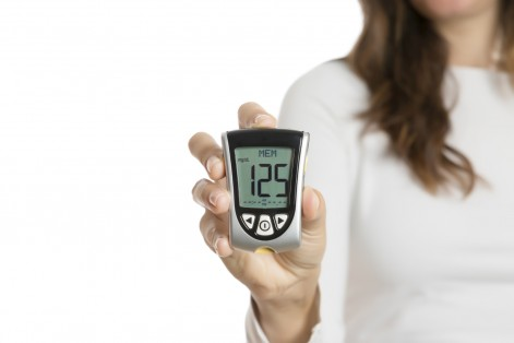 closeup of a hand of a woman holding a glucometer isolated on a white background