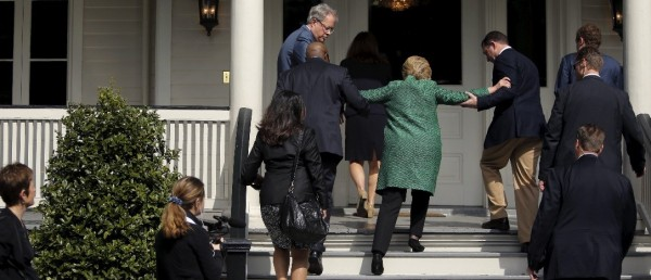 Clinton being helped up stairs