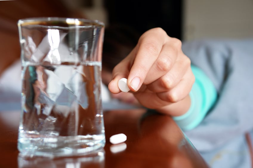 Woman with a flu taking pill