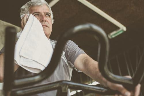 Man on Treadmill Wiping Sweat