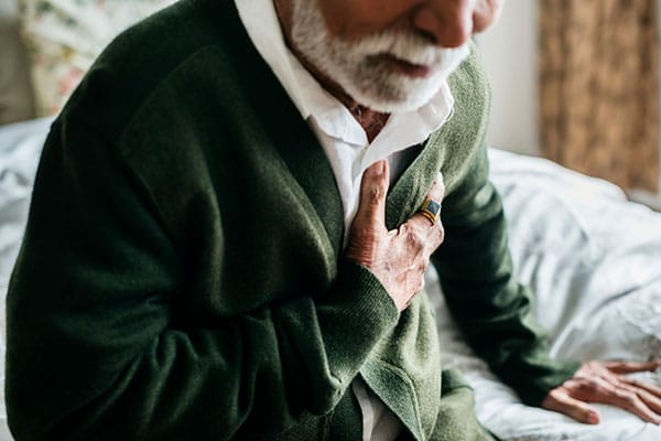 Photo of man grabbing chest.