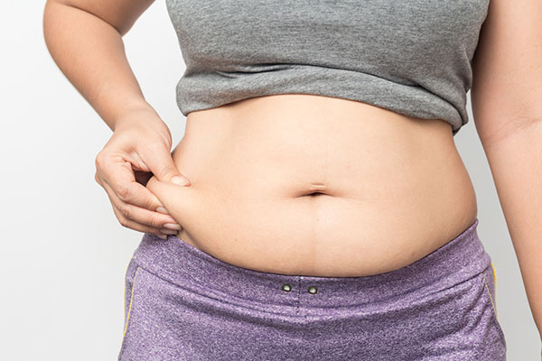 Photo of woman pinching her belly fat.