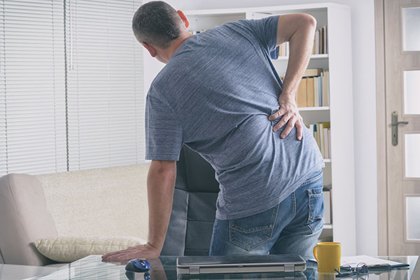 Photo of man holding back in pain.