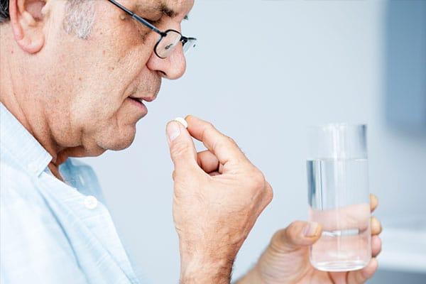 Photo of person taking medicine.