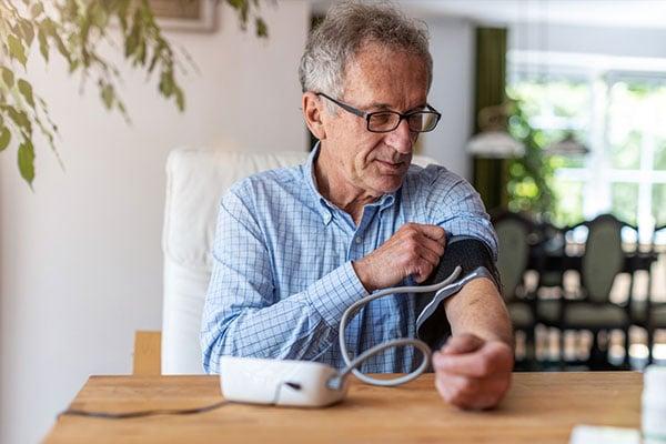 Photo of man taking blood pressure.