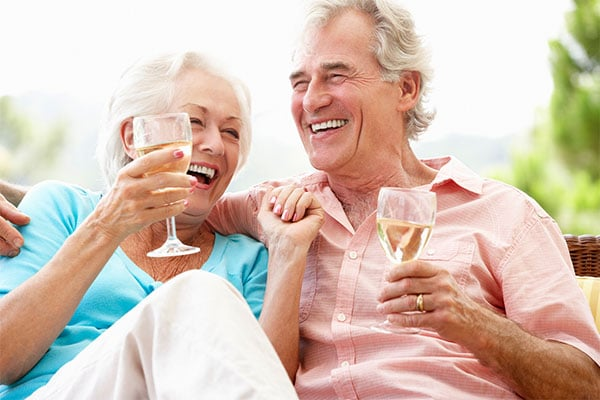 Photo of couple laughing and drinking wine.