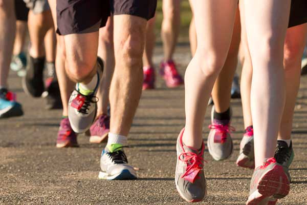 Image of many peoples legs in tennis shoes running in a group.