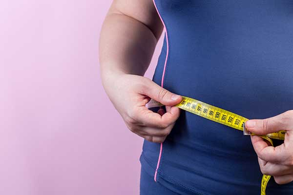 Upclose picture of a person measuring their midsection with a tape measure.