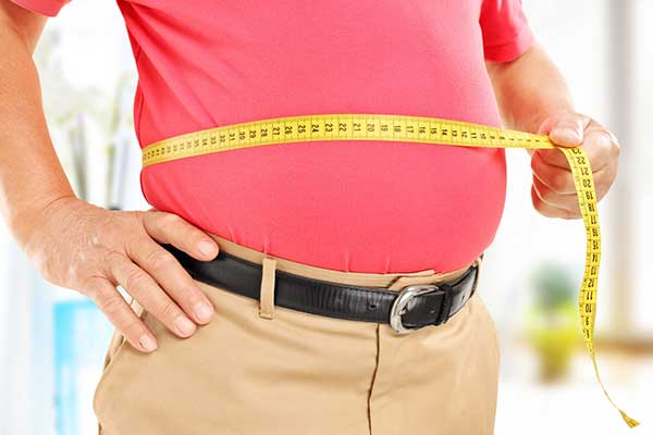 A men in a red shirt measuring his waistline with a measuring tape.