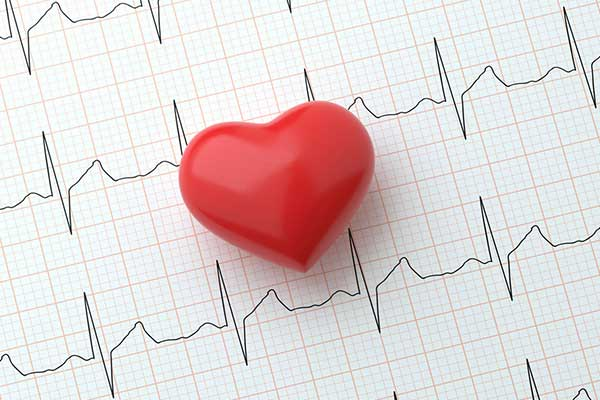A red heart sits on a paper of ekg readings.