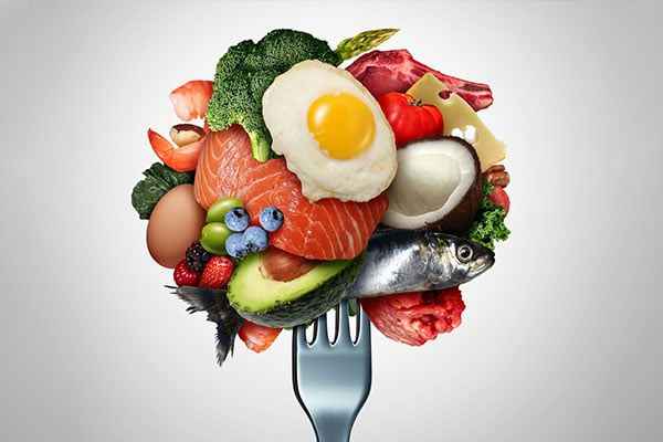 Picture of an arrangement of vegetables and other food on a fork.